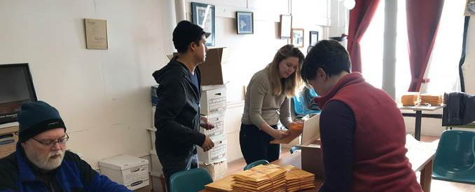 a group stuffs envelopes with a journal