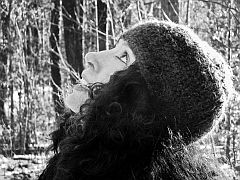 a black and white image of Meg Kearny looking skyward with a forest in the background