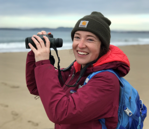 Jamie Samdahl on a beach holding binoculars.