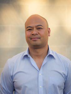Oliver de la Paz wearing a blue button down shirt