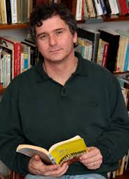 A man wearing a dark green polo shirt holds an open yellow book in front of a bookcase filled with many volumes