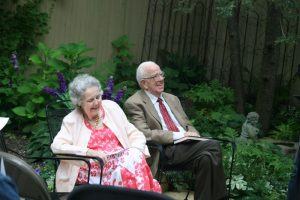Two figure seated in a garden setting. Mary Pat True (left) and Mike True (right)