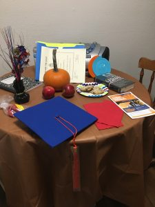 A table covered with a brown table cloth has multiple gifts including 2 apples, a blue graduation cap with an orange tassle, balloons, and a book
