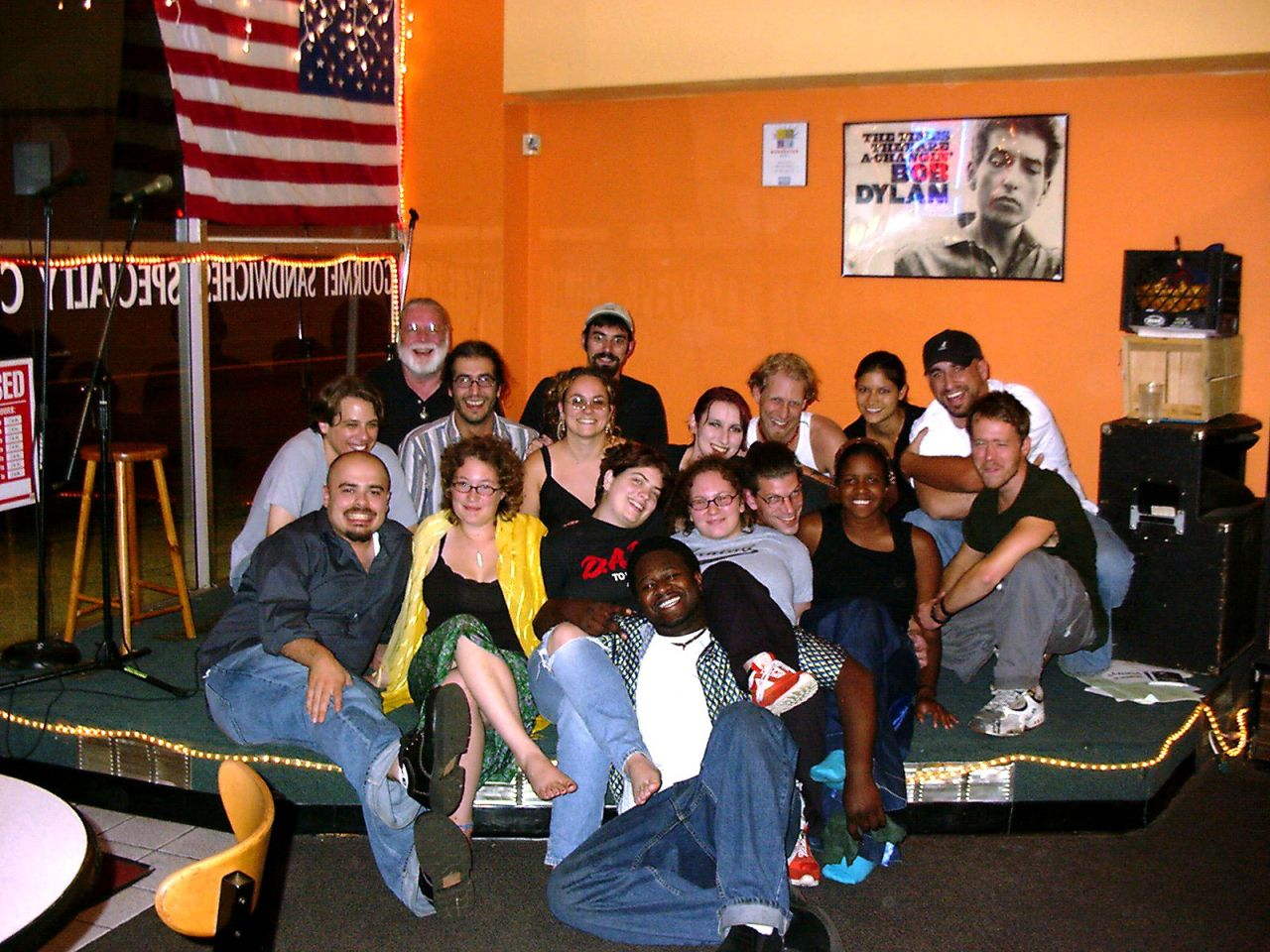 a group photo 17 people seated on a stage inside a store