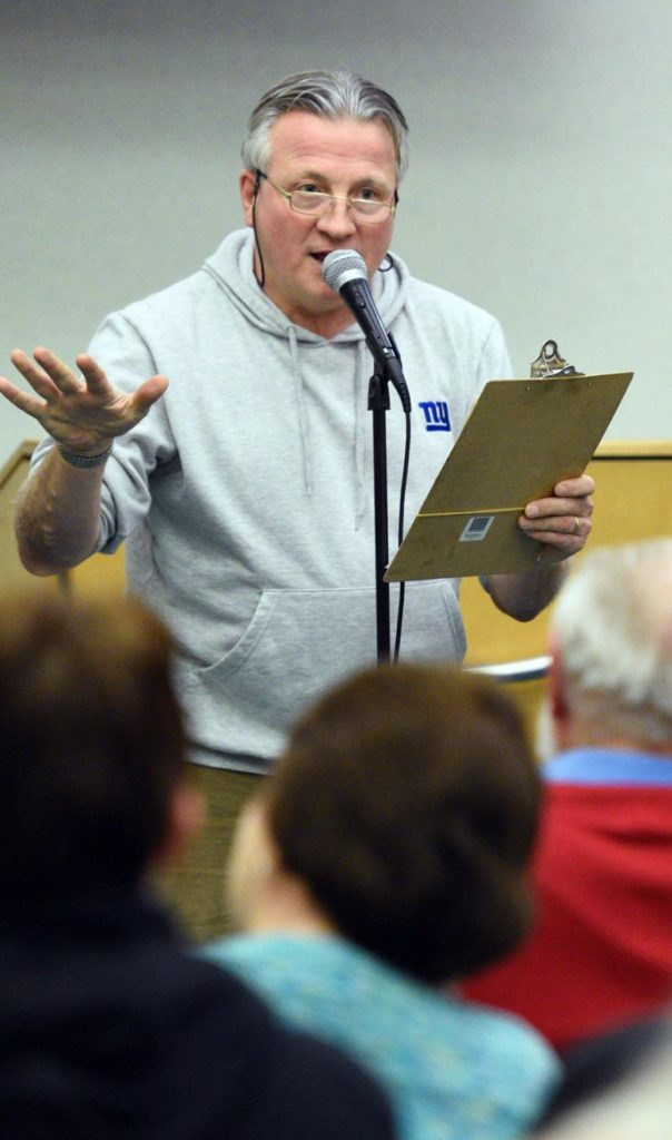A man, Joe Fusco Jr., stands in front of a microphone with a clipboard. He is gesturing with his right hand toward an audience that can be seen in the foreground. He wears a gray hoodie and glasses.