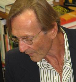 A man with metal-framed glasses, wearing a striped shirt and a charcoal colored blazer, looks across his left shoulder toward the floor.