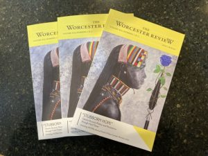 """3 copies of """"The Worcester Review"""" literary journal are fanned out on a dark green surface"""